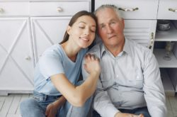 Old man in a kitchen with young granddaughter